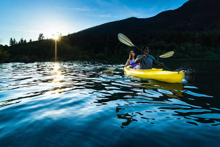 lake shore: Couple paddling in kayak on lake. Stock Photo
