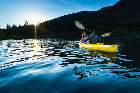 canoe paddle: Couple paddling in kayak on lake. Stock Photo