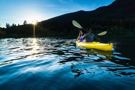 canoa: Pareja remando en kayak en el lago.