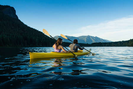 Couple paddling in kayak on lake.