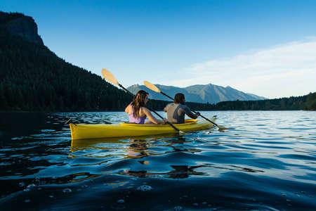 piragua: Pareja remando en kayak en el lago.