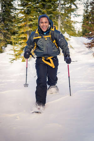 snowshoeing: Young black man on snowshoe hike. Stock Photo