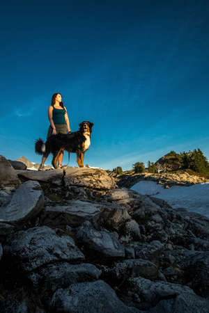 Beautiful women hiking with her Bernese Mountain dog in the mountains.
