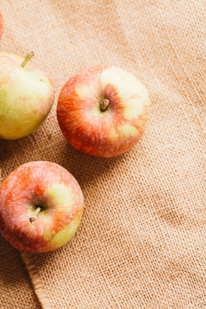 sacking: several fresh red apples on sacking background.