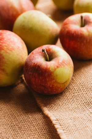 apple sack: several fresh red apples on sacking background.