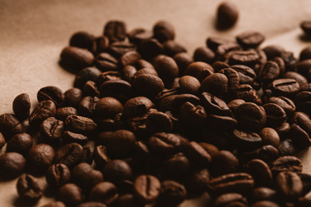 colombian food: dark coffee beans close-up on light paper close up.