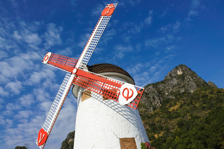 Windmill of Swiss Sheep Farm with blue sky and big mountain in the background in Cha-am, Thailand photo