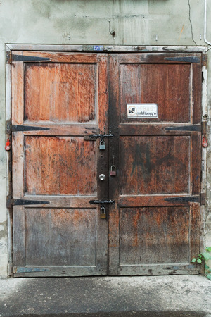 Old closed door with 3 locks found in soi of downtown of Bangkok, Thailand photo
