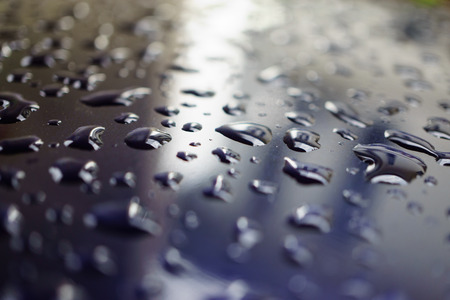 surface tension: A lot of dew drops on remain on the blue metal surface after raining
