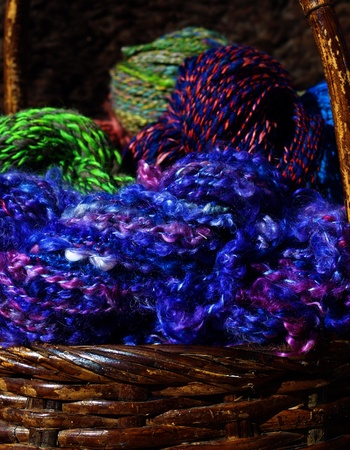 Colorful hand spun yarn overflows from a basket.
