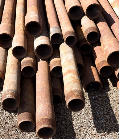 A close-up of rusted pipes with finely detailed threads stacked up on a site on a sunny spring day in Central Oregon.