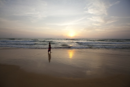 Girl Walking On The Beach At Sunset photo