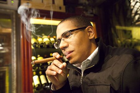 Young Hispanic Man Smoking A Cigar Stock Photo - 14185539