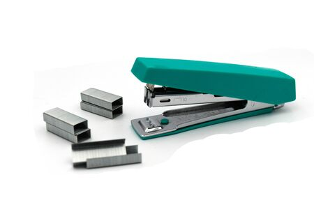 Green Max stapler with staple paper.A stapler is a mechanical device that joins pages of paper or similar material by driving a thin metal staple through the sheets and folding the ends. Banque d'images
