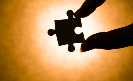 hand holding a puzzle piece, which is illuminated backlit photo