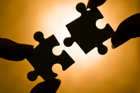 hands trying to fit two puzzle pieces together. photo