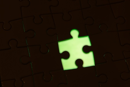 missing one piece of the puzzle on a green background Stock Photo - 18530872