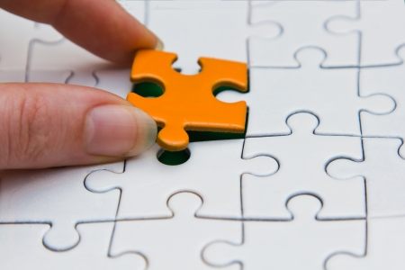 final piece of puzzle: Hands placing last piece of a Puzzle