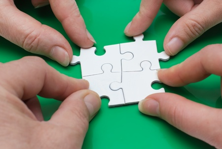 Close up of four people hands with puzzle photo