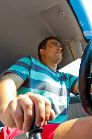 lever: driver sitting behind the wheel, the gear lever switches Stock Photo
