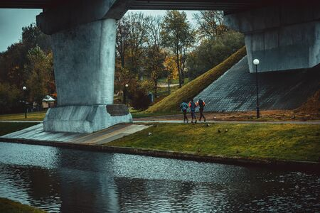 Three people jogging near the river