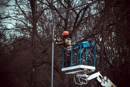 the master repairs the lamppost standing on aerial platform among the trees