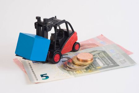 warehousing: Toy forklift hauling a wooden blue cube with coins and euro notes