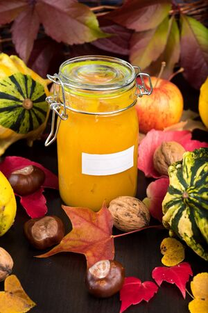 autumn food: Closeup of Jar of homemade jam with blank label among autumn leaves and nuts on dark table background