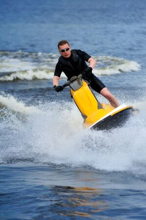 Young man riding yellow jet ski