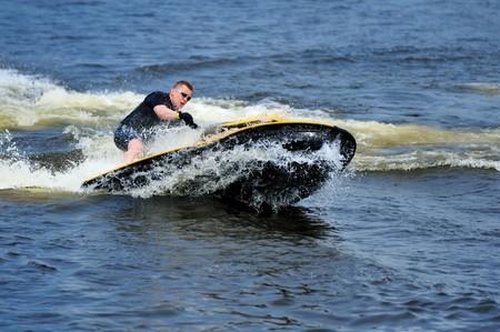 Young man riding yellow jet ski