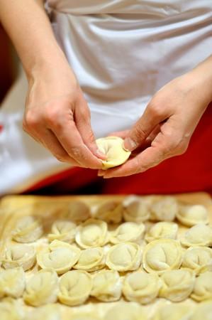 Woman making russian dumplings (pelmeni), focus on hands 版權商用圖片