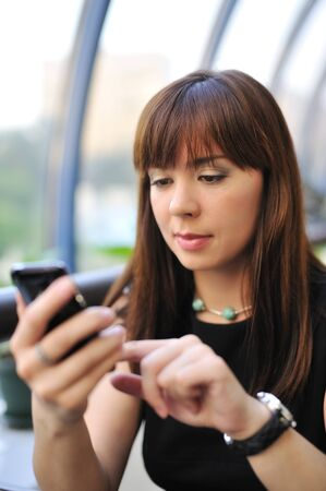 Attractive young woman using her pda 写真素材