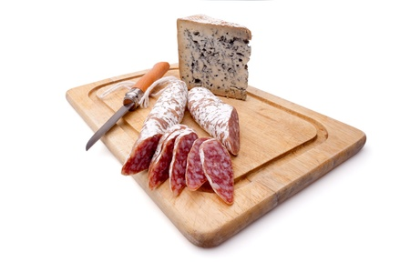 Rustic still life with cutting board, smoked sausage, matured blue cheese and folding knife Stock Photo