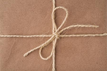 gefesselt: String gebunden in einem Bogen, auf einem braunen Recycling-Papier-Paket