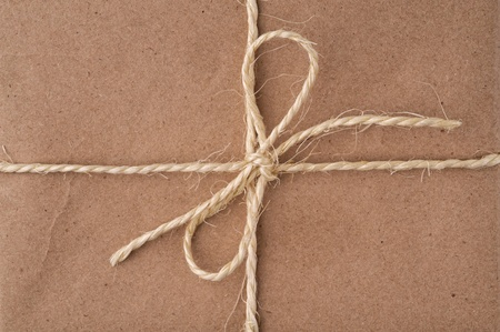 twine: String tied in a bow, on a brown recycled paper package