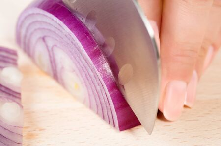 Female hands with knife, cutting fresh onion