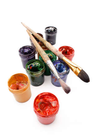 Goup of opened cans with multicolored paints, and brushes, white background photo