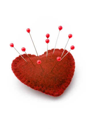 Red heart, studded with a lot of pins, love or health concept, white background Stock Photo
