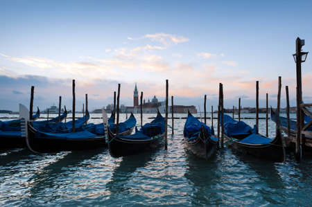 Early morning over the Venice Grand Canal. Famous Venice gondolas at the foreground, Church of San Giorgio Maggiore at the background. photo