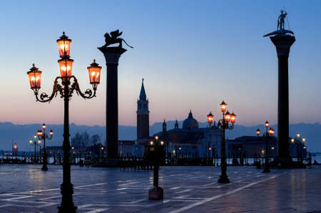 Morning at San Marco square. Saint Theodore and Lion of Saint Mark columns, and famous Venetian street-lamps. Church of San Giorgio Maggiore at the background. photo