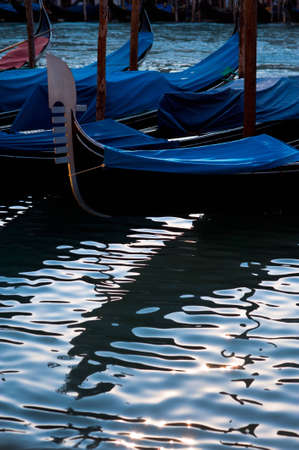 Venetian gondolas, with silhouette reflection in water photo