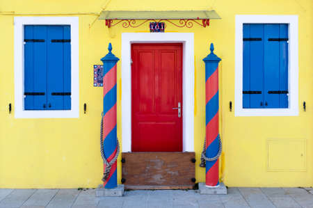Colorful house entrance - bright yellow wall with blue windows and red door  photo