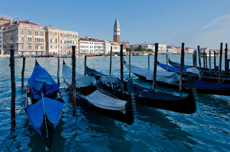 Venetian gondolas, with silhouette reflection in water. San Marco Campanile at background. photo