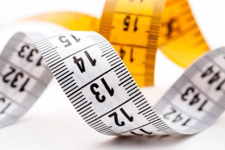 tailor measure: Metri su misura giallo e bianco su sfondo bianco, closeup girato