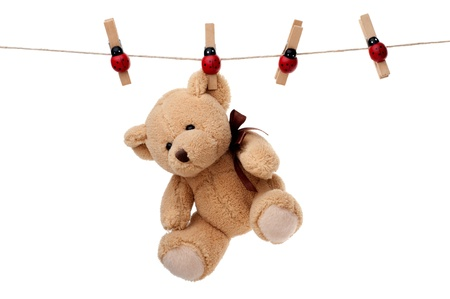 Small teddy bear hanging on clothesline, isolated on white background 写真素材