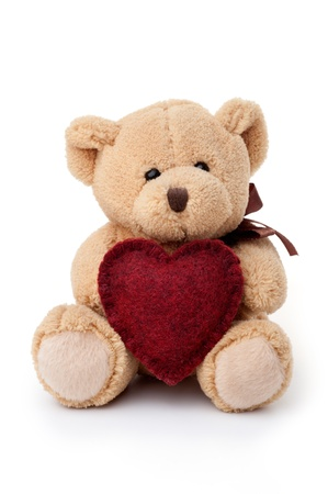 Small teddy bear holding red heart, sitting, isolated on white background
