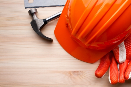 Home repair: Hardhat, gloves and some assorted tools arranged on a wooden surface. Construction, repair or home improvement background.