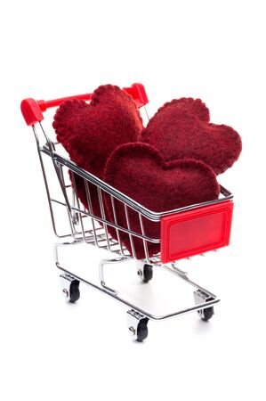 Shopping cart, full of red hearts, isolated on white background photo