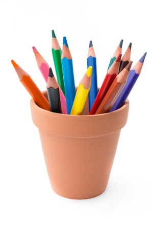 Drawing supplies: assorted color pencils in ceramic pot, isolated on white background
