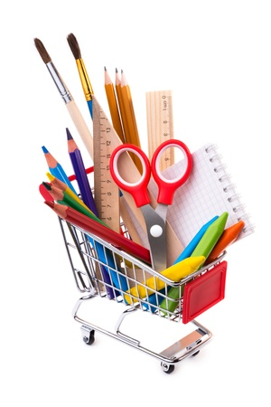 School supplies: assorted crayons, paintbrushes, pencils, pastels, rulers and notebook in a shopping cart, isolated on white background